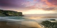 Sunset over sandy beach with cliffs, Santander, Cantabria, Spain