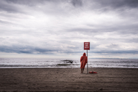 Man in orange raincoat leaning on banner on beach, Brighton Beach, New York City, New York State, USA