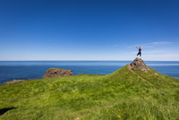 Woman raising hands on hill, Newfoundland, Canada