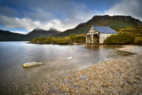 Old wooden lakeside building surrounded by mountains, Tasmania, Australia
