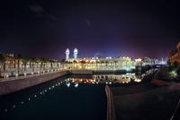 Swimming pool and remote King Abdullah Grand Mosque at night, Thuwal, Saudi Arabia