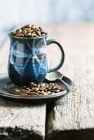 Coffee beans in mug on wooden table