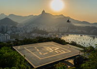 Mountain landscape with helicopter landing on heliport at sunset, Brazil