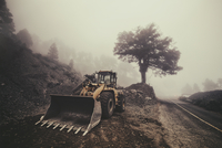 Earth mover standing by road in fog