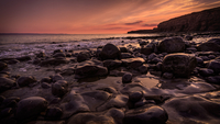 Rocky beach with remote cliff at sunset
