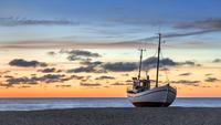 Fishing boat on Slettestrand beach at sunset, Fjerritslev, Jammerbugt Municipality, Denmark