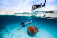 Snorkeling woman next to sailing boat, Maldives, Spain
