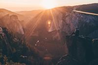 Man sitting on rock edge in mountain, California, USA
