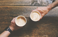 Hands holding coffee cups with latte art