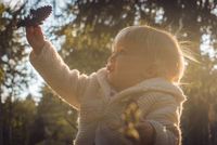 Little girl (12-23 months) holding pine cone