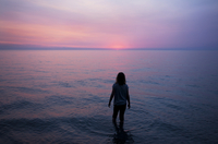 Woman standing in water at sunset, Ontario, Canada