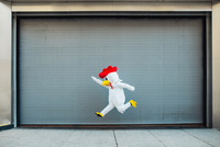 Person in chicken costume jumping on street