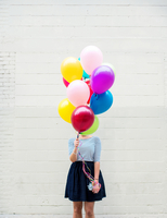 Woman hiding behind colorful balloons against white brick wall 11098073232| 写真素材・ストックフォト・画像・イラスト素材|アマナイメージズ