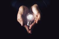 Hands holding shining electric bulb 11098073238| 写真素材・ストックフォト・画像・イラスト素材|アマナイメージズ