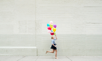 Woman running down street holding bunch of colorful balloons