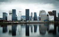 Skyscrapers reflecting in calm river, Oslo, Norway