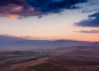 Rural landscape and remote mountains at sunset, Tuscany, Italy