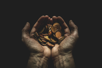 Hands holding coins against black background