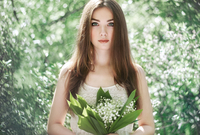 Portrait of beautiful young woman with lily of the valley