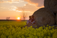 Two children, boy brothers in a oilseed rape field, sitting on a 11098078326| 写真素材・ストックフォト・画像・イラスト素材|アマナイメージズ
