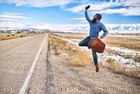 happy hitch hiker with beard and smart phone jumping for joy beside empty road in nevada