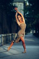 Young beautiful ballerina dancing on the sidewalk