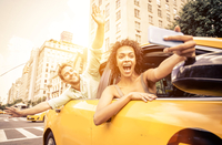 Happy couple driving in New york on a yellow cab and taking self 11098078440| 写真素材・ストックフォト・画像・イラスト素材|アマナイメージズ
