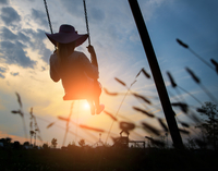Woman playing on a swing at sunset