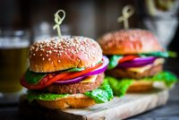 Homemade burgers on rustic wooden background