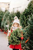 Girl holding a Christmas tree at the market. 11098082580  写真素材・ストックフォト・画像・イラスト素材 アマナイメージズ