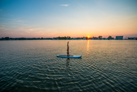 Young woman on a SUP board doing yoga at sunset 11098082685| 写真素材・ストックフォト・画像・イラスト素材|アマナイメージズ