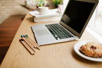 Laptop and baked good on a desk. 11098082910| 写真素材・ストックフォト・画像・イラスト素材|アマナイメージズ