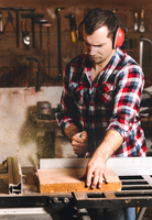 Carpenter working on an electric buzz saw cutting some boards