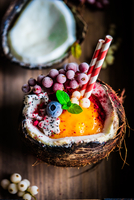 Mango smoothie in a coconut shell with berries and fruits on rus