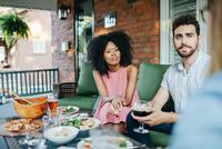 Young adults sitting on veranda drinking alcohol 11098083297| 写真素材・ストックフォト・画像・イラスト素材|アマナイメージズ