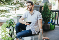 Young men sitting outdoors having a conversation 11098083305| 写真素材・ストックフォト・画像・イラスト素材|アマナイメージズ