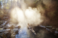 Young woman lying in steaming hot spring,