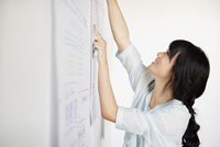 Woman hanging blueprint on wall