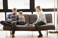Parents with daughter (4-5) using digital devices at home