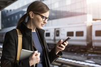 Woman with mobile phone on railroad station 11100000372| 写真素材・ストックフォト・画像・イラスト素材|アマナイメージズ