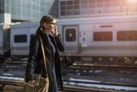 Woman with mobile phone on railroad station 11100000373| 写真素材・ストックフォト・画像・イラスト素材|アマナイメージズ