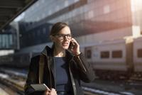 Woman with mobile phone on railroad station 11100000374| 写真素材・ストックフォト・画像・イラスト素材|アマナイメージズ