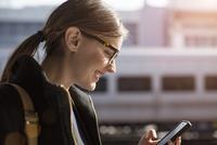 Woman with mobile phone on railroad station 11100000375| 写真素材・ストックフォト・画像・イラスト素材|アマナイメージズ