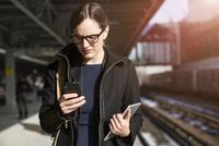 Woman with mobile phone on railroad station 11100000376| 写真素材・ストックフォト・画像・イラスト素材|アマナイメージズ