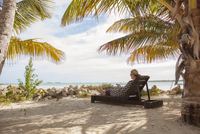 Woman reading on beach chair under palm tree
