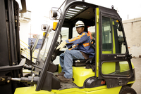 Portrait of industrial worker operating forklift