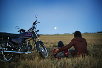 Father with son (4-5 ) sitting in field and looking at moon