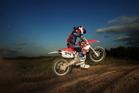 Motocross rider jumping on motorcycle