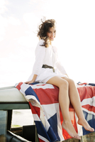 Portrait of young woman sitting on roof of car covered with British flag 11100001445| 写真素材・ストックフォト・画像・イラスト素材|アマナイメージズ