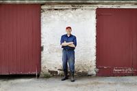 Portrait of farmer by barn doors